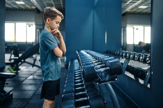 소년 체육관에서 무거운 아령을 시도합니다. 스포츠 클럽, 건강 관리 및 건강한 라이프 스타일 훈련, 운동 모범생