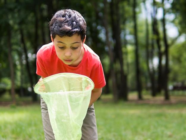 Мальчик пытается поймать бабочек