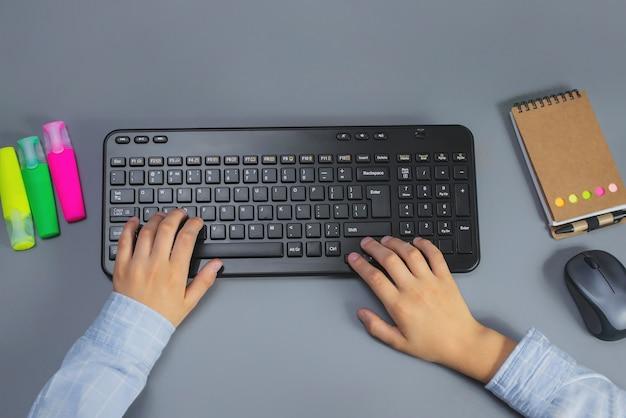 Мальчик печатает на клавиатуре на рабочем столе