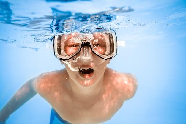 プールの水の下で少年