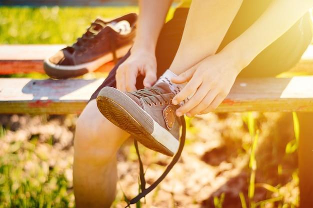 Boy untying laces on sneakers