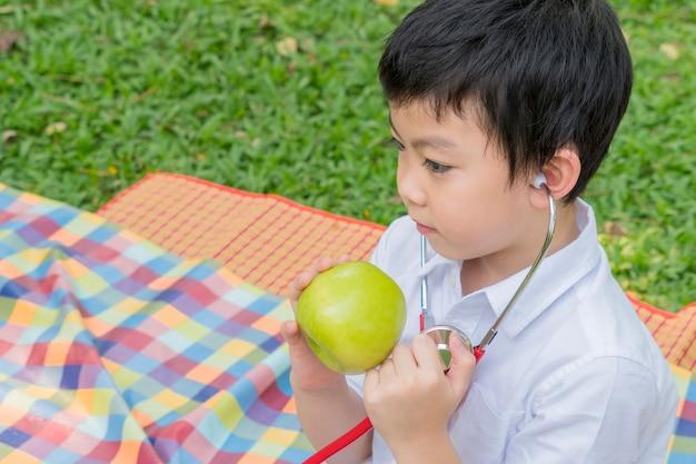 少年は聴診器を使用し、果実の緑リンゴのシンボルで遊ぶ