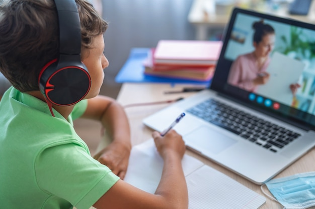 Boy uses laptop to make video call with his teacher