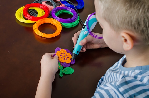 Boy using 3d pen. happy child making flower from colored abs plastic