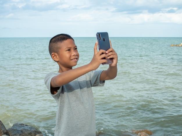 海の背景で自分撮りをするために電話を使用している少年