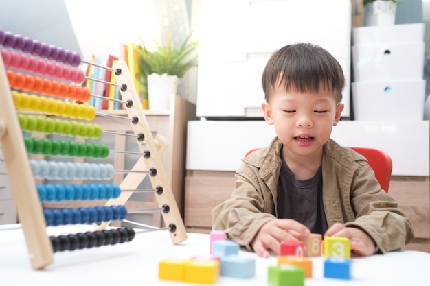 Boy using the abacus with beads and wooden brick with numbers