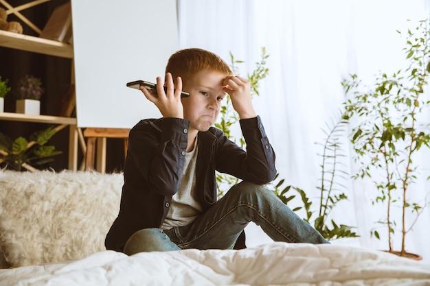 家でさまざまなガジェットを使用している少年。スマートウォッチ、スマートフォンまたはタブレットとヘッドフォンを備えた小さなモデル。自撮り、チャット、ゲーム、ビデオ鑑賞。子供たちと現代のテクノロジーの相互作用。