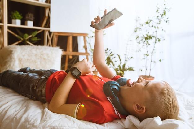 家で別のガジェットを使用している少年。スマートウォッチ、スマートフォンまたはタブレットとヘッドフォンを備えた小さなモデル。自撮り、チャット、ゲーム、ビデオ鑑賞。子供と現代のテクノロジーの相互作用。