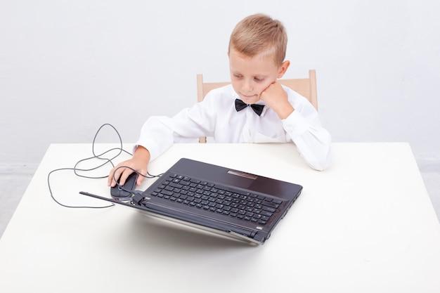그의 랩톱 컴퓨터를 사용하는 소년
