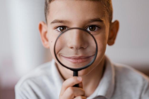 Boy using a magnifier in class