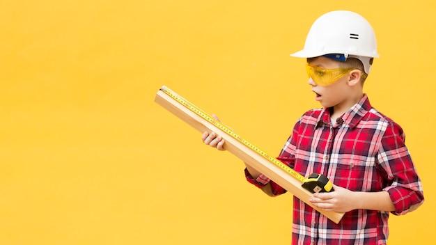 Boy using measuring tape copy space