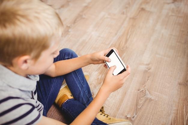 Boy using mobile phone while sitting on hardwood floor