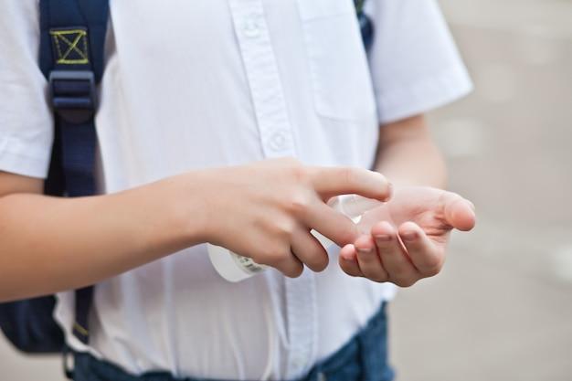 학교에서 손을 소독하기 위해 소독제나 소독제 스프레이를 사용하는 소년. 코로나바이러스 검역, 전염병 예방 개념.