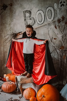 Boy vampire dracula costume for halloween stands among pumpkins. children celebrate halloween in festive scary creepy decorations