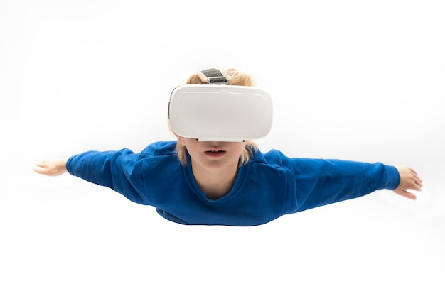 Boy in virtual reality glasses flies on white surface. virtual reality games, vr glasses.