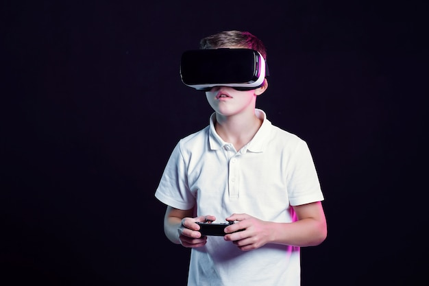 Boy in vr goggles playing with gamepad