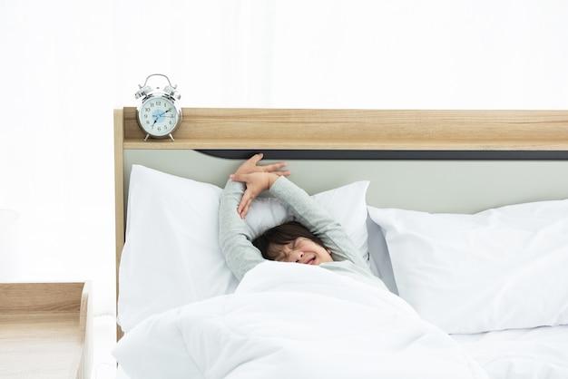 Мальчик просыпается и растягивается на кровати утром с будильником.