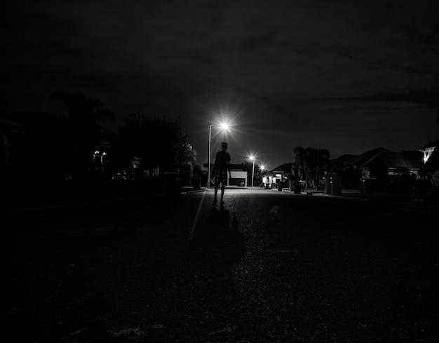 가로등 아래에서 밤에 혼자 걷는 소년