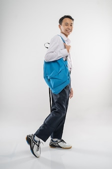 A boy walking in junior high school uniform smiling with carrying a backpack