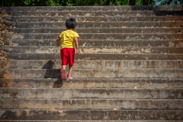 Boy walking up the concrete stairs