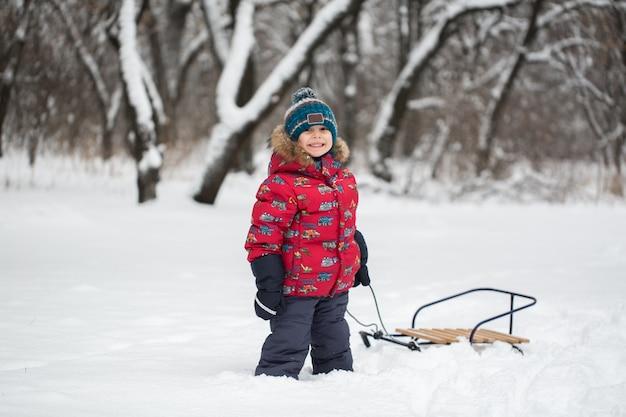 Мальчик гуляет с санками в заснеженном зимнем лесу