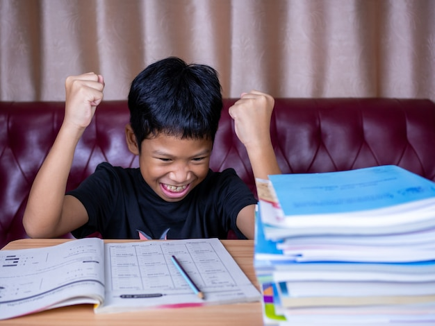 The boy was very happy to finish his homework. he sat on a wooden table and had a stack of books next to it. the background is a red sofa and cream curtains.