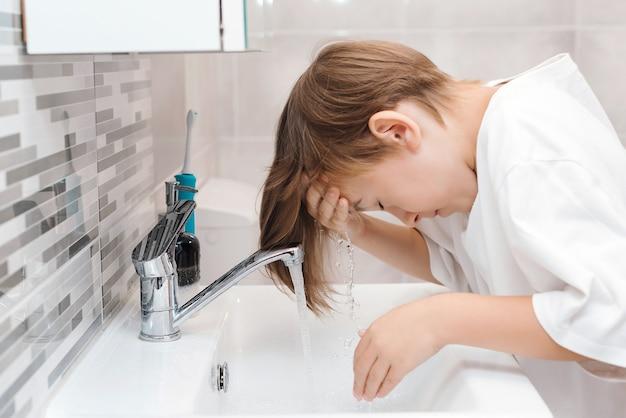 男の子がトイレで顔を洗う。朝の衛生。プレティーンの少年は洗面台で洗われます。