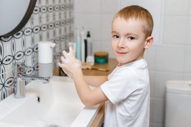 센서 비누 디스펜서를 사용하여 화장실에서 손을 씻는 소년.