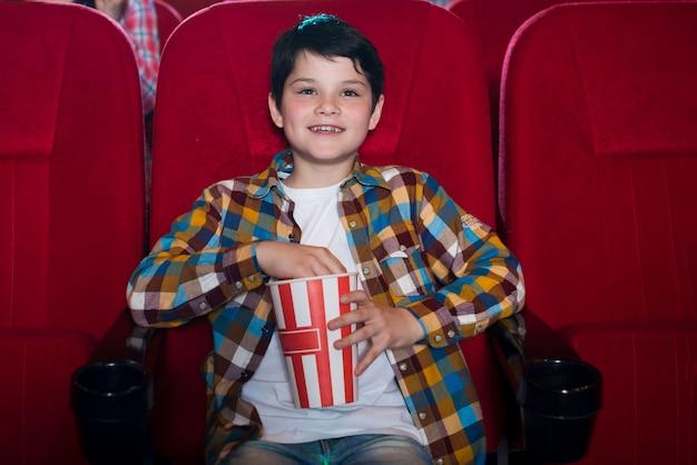 映画館で映画を見ている少年