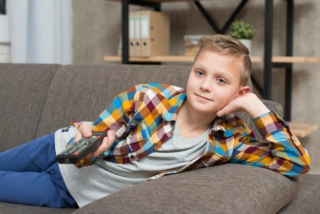 Мальчик смотрит телевизор на диване Бесплатные Фотографии
