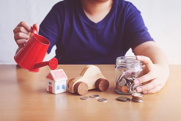 Мальчик поливает машину и дом и монеты. план для концепции дома