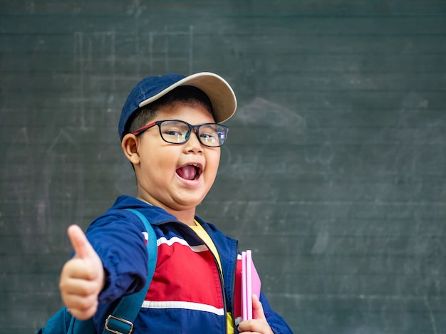 Boy wear glasses smiling and stand in front of the blackboard. back to school.