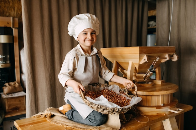 Boy wearing an apron sitting on a table holding a big basket of corn seeds
