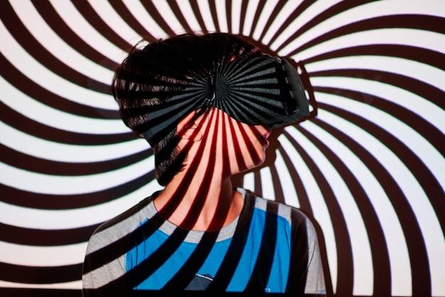 スパイラル投影された背景に拡張現実メガネをかけている少年
