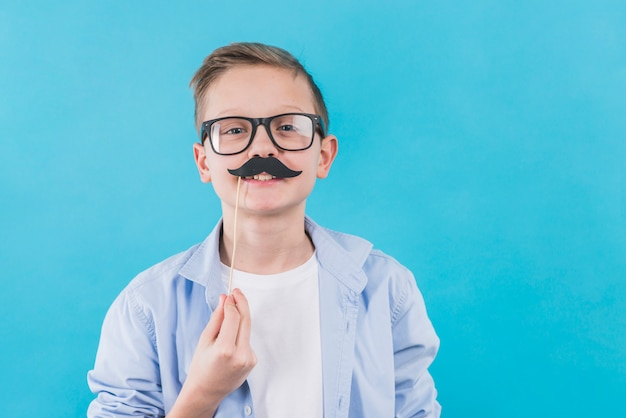 A boy wearing black eyeglasses holding black moustache prop in front of his upper lips