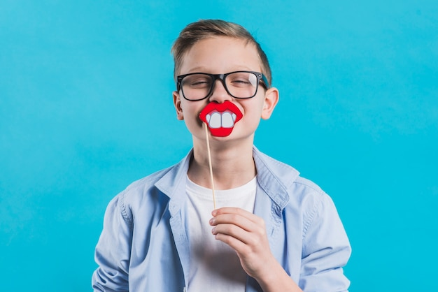 A boy wearing black eyeglasses holding smiling prop in front of his mouth against blue background