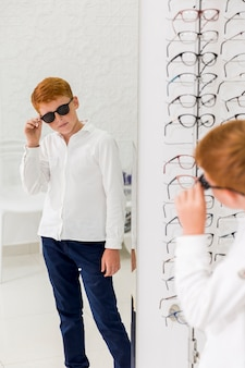 Boy wearing black eyeglasses and looking in mirror at optics store