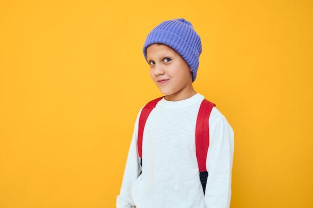 黄色の背景のポーズをとって青い帽子の学校のバックパックを身に着けている少年