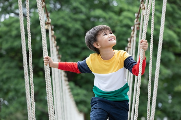 Boy wearing bright colour clothes walking alone on rope bridge at extreme sport in adventure park