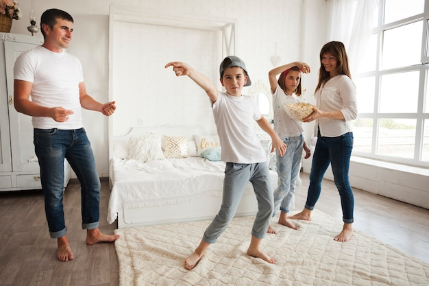 Boy wearing cap and dancing in front of his parents and sister at home