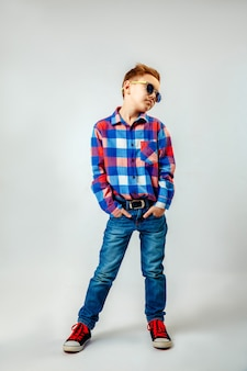Boy wearing colorful plaid shirt, blue jeans, gumshoes, sunglasses, posing and having fun