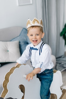 Boy wearing a crown , a happy boy riding a horse like a prince, a concept of creativity for staying at home.