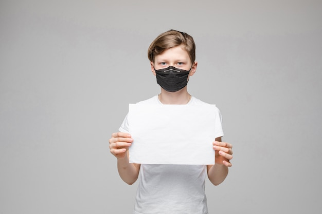 Boy wearing face mask holding blank sign