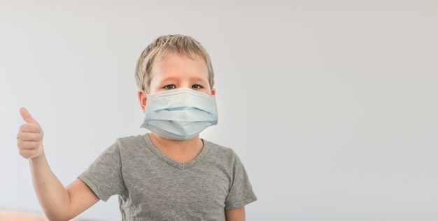Boy wearing facial disposable mask to avoid viral infection. stop coronavirus