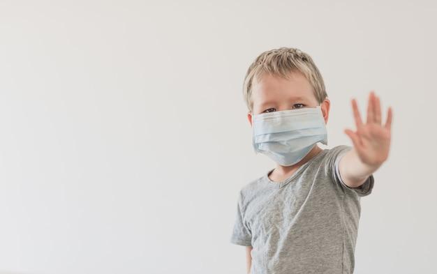 바이러스 감염을 피하기 위해 얼굴 일회용 마스크를 착용하는 소년. 코로나 바이러스 중지