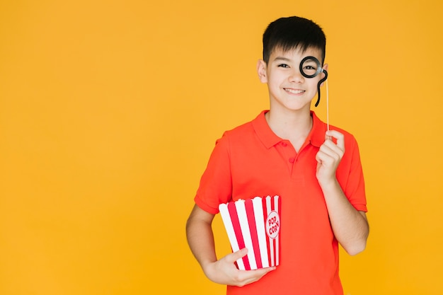 Boy wearing a fake monocle with copy space