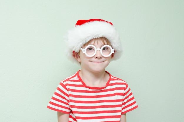 Мальчик в очках и шляпе санта-клауса стоит на фоне светлой стены. портрет.