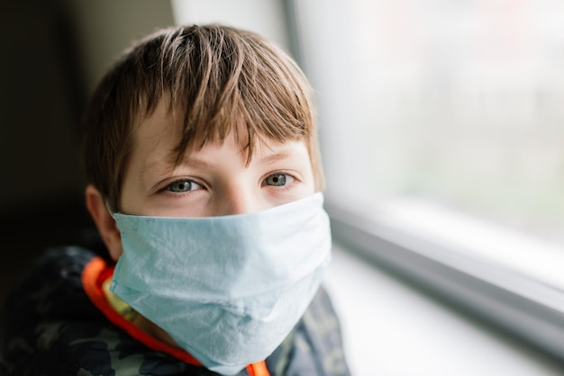 Boy wearing medical face mask, protective measures against spreading of covid-19