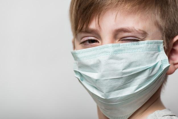 医療用マスクを着ている少年。フェイスマスクの子がウィンクします。肖像画のクローズアップ