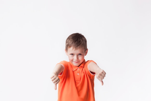Boy wearing orange t-shirt showing dislike gesture against white backdrop